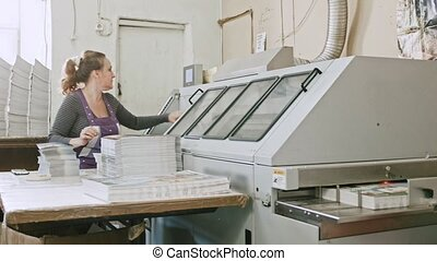 Manual labor - polygraph printing process - a woman completes a paper for a magazine, wide angle