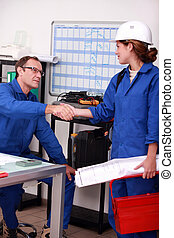 Manual laborers shaking hands in an office