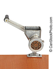 Manual meat grinder on wooden table and white background.