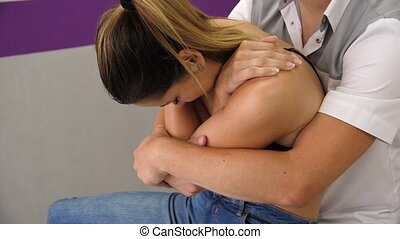 Manual therapist massaging and examining a young woman stretching her spine. A chiropractor sets the compression of the vertebrae sharp and choppy.