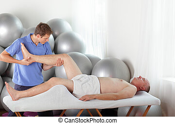 manual therapy - young physiotherapist bending male patient knee during massage