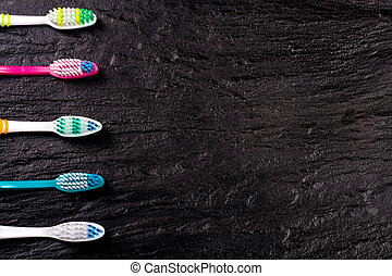 manual toothbrushes on the black background with copy space for your text. Top view
