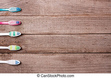 manual toothbrushes on the old wooden background top view