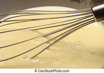 Manual whisk mixing cream and egg for cooking dessert