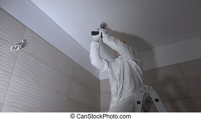 manual worker drilling hole in ceiling plasterboard for led...