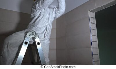 manual worker drilling hole in ceiling plasterboard for led lighting mounting