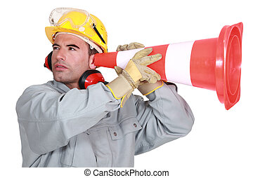 Manual worker holding traffic cone to ear