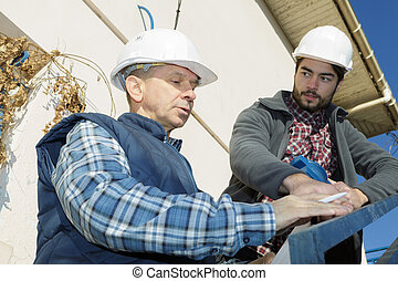 manual worker with clipboard showing something to co-worker