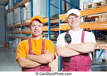 manual workers crew in warehouse - two young handsome...