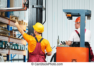 manual workers in warehouse - two young workers man in...