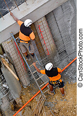 Manual workers inspecting a concert wall in construction site