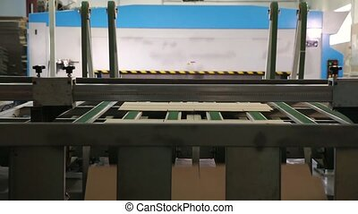 Manufacture of cardboard boxes. Machine carves cardboard...