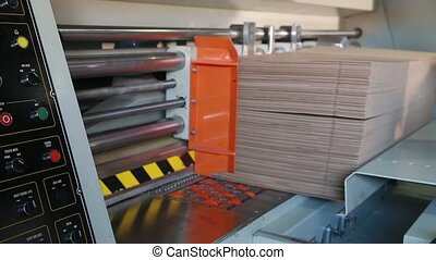 Manufacture of cardboard boxes. - Workers put sheets of...