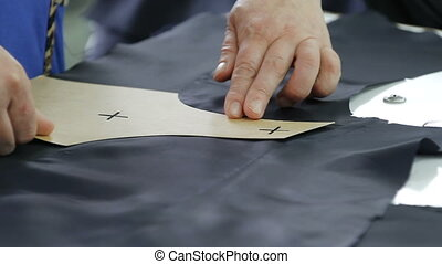 Tailor at work, drawing line on fabric with chalk.