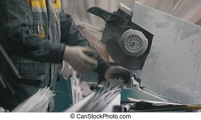 Manufacture of composite fiberglass reinforcement - worker cuts wires with circular saw