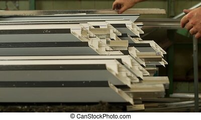 Manufacturing windows pvc, male worker inserts a metal ...