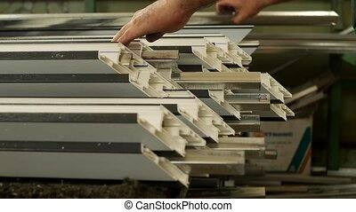 Manufacturing windows pvc, male worker inserts a metal...