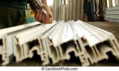 Manufacturing windows pvc, male worker twists screws in the...