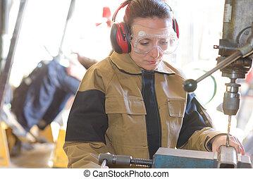 manufacturing worker operating a machine