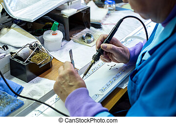 Manufacturing. Worker soldering circuit board -...