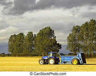 a blue tractor spreading manure on a stubble field