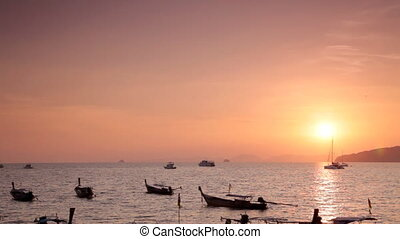 Many anchored boats on the sea with sunset behind