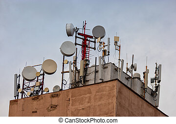 Many Antennas on the top of building in the city