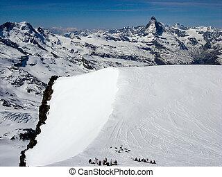 many back country skiers on a high summit plateau in the Swiss Alps near Zermatt