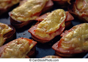 Many baked hot sandwiches with ham and cheese lie on a tray in a row.