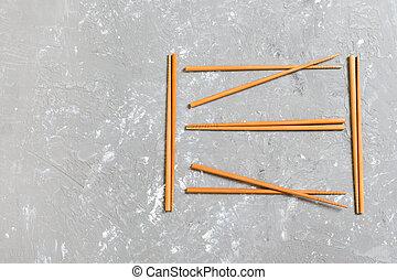 Many bamboo chopsticks on black cement stone