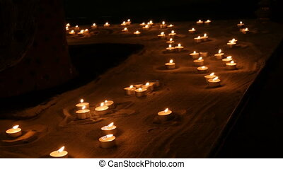 Many beautiful, round, small white candles burning in the...