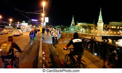 Many bicyclists ride over bridge near Kremlin in Moscow