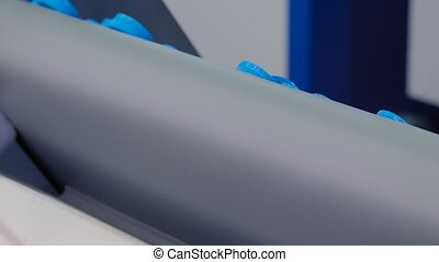 Many blue plastic bottle caps falling from conveyor belt at exhibition, factory - production line - close up. Manufacturing, recycling, industry, technology equipment concept