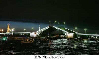 Many boats float near shined Palace Bridge