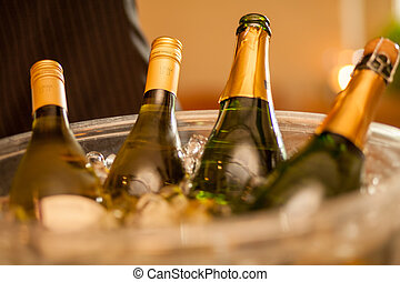 Many bottles of champagne on blurred background, closeup