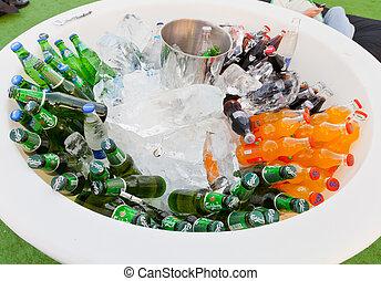 many bottles of soft drinks in white bowl