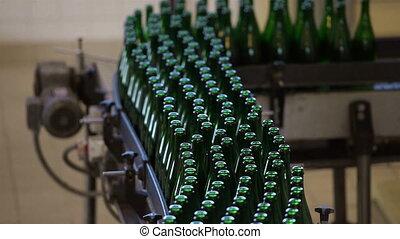 Many bottles on conveyor belt in factory
