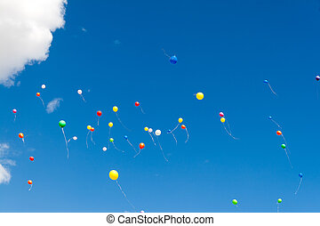 many bright baloons in the blue sky