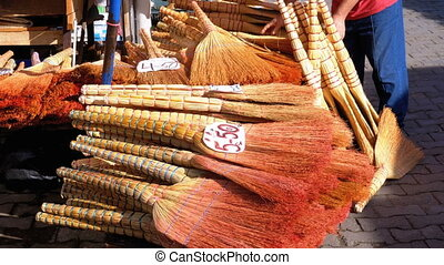 Many brooms lie on the counter of the market with a price...