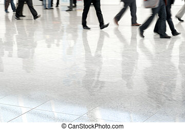 Many business people in blurred motion in a fair hall
