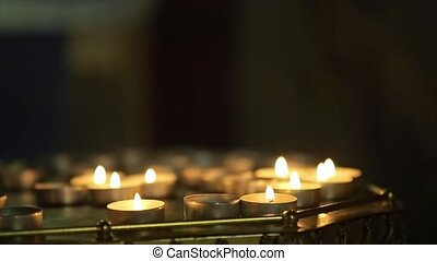 Many Candle Flames Glowing in the Dark Church create a...