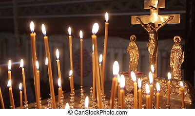 Religion - Many candles are lit next to the Christian cross....
