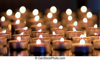 Many candles lighting in night. Shallow depth of field dolly shot