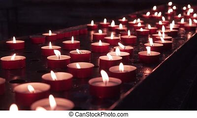 Many candles lit on a metal surface