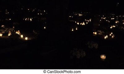Many candles on graveyard at all dead day at night. Panorama. 4K