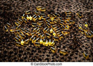 many capsules of gold color lies on the leopard skin