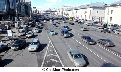 Many cars ride Sadovoe Ring in Moscow, people walk around