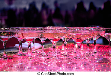 Many Champagne glasses at party are lined up ready to be served. Celebrate, cheer, cocktail in the background. Elegant catering, tiered alcohol drinks on glass table in luxury purple concept