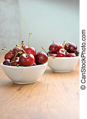many cherries in a white bowl