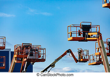 Many cherry pickers against a blue sky